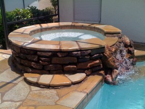 custom-natural-stone-hot-tub-runs-into-pool